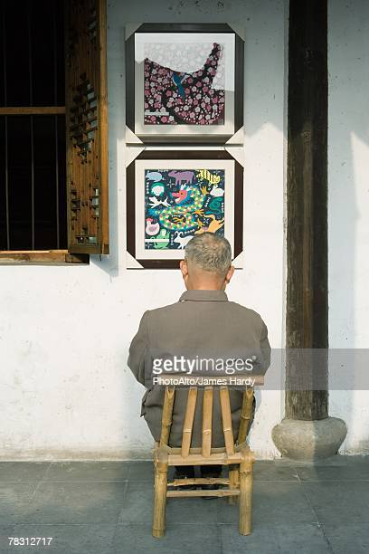 Man sitting in chair, facing wall with framed pictures, rear view