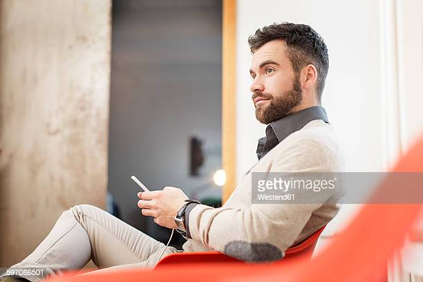 Man sitting in chair holding cell phone