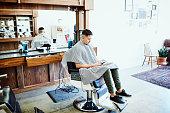 man sitting chair barber shop working