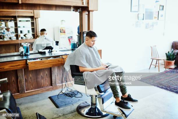 Man sitting in chair in barber shop working on smartphone waiting for hair cut