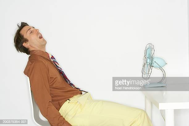 Man sitting in chair, in front of fan, eyes shut