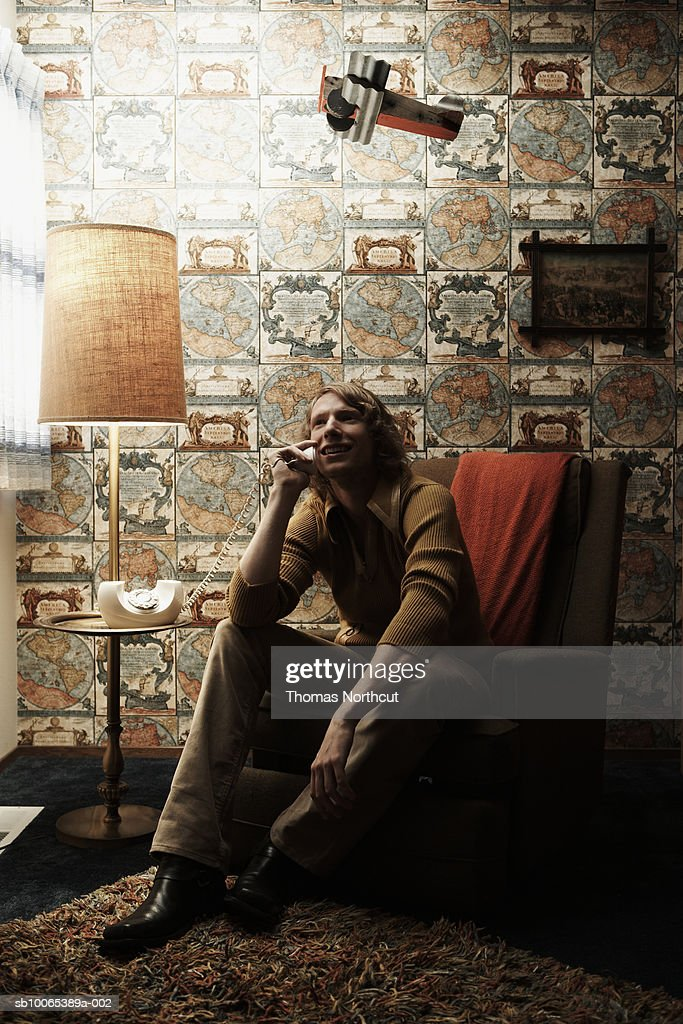Man sitting in chair in room, talking on phone : Stock Photo