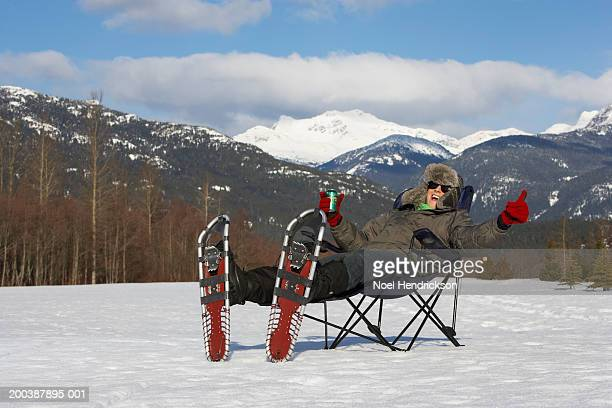 Man sitting in chair in snow, wearing snow shoes, smiling