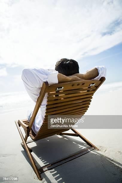 Man sitting in chair on beach hands, hands behind head, rear view