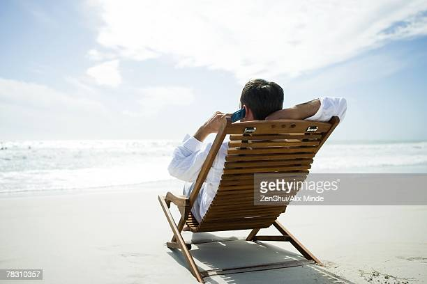 Man sitting in chair on beach, using cell phone, rear view