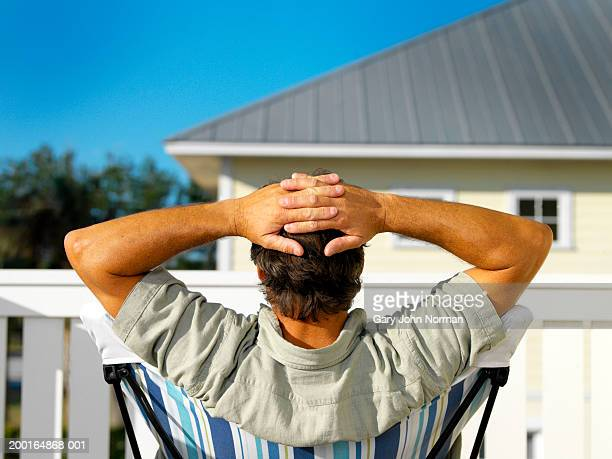 Man sitting in chair on deck of house, hands behind head