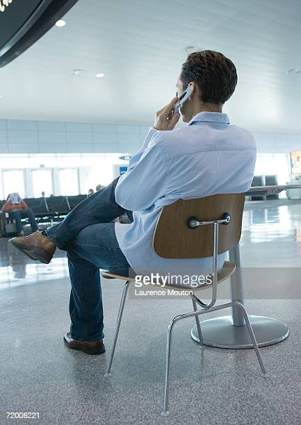 Man sitting in chair using cell phone