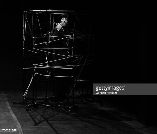 Man Sitting In Chariot On Stage Against Black Background