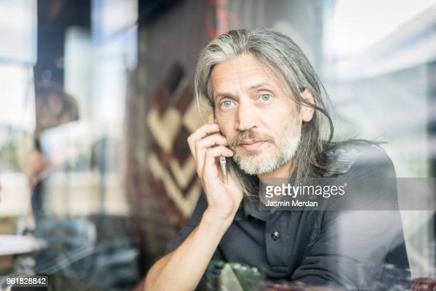 Man sitting in coffeeshop and using smart phone