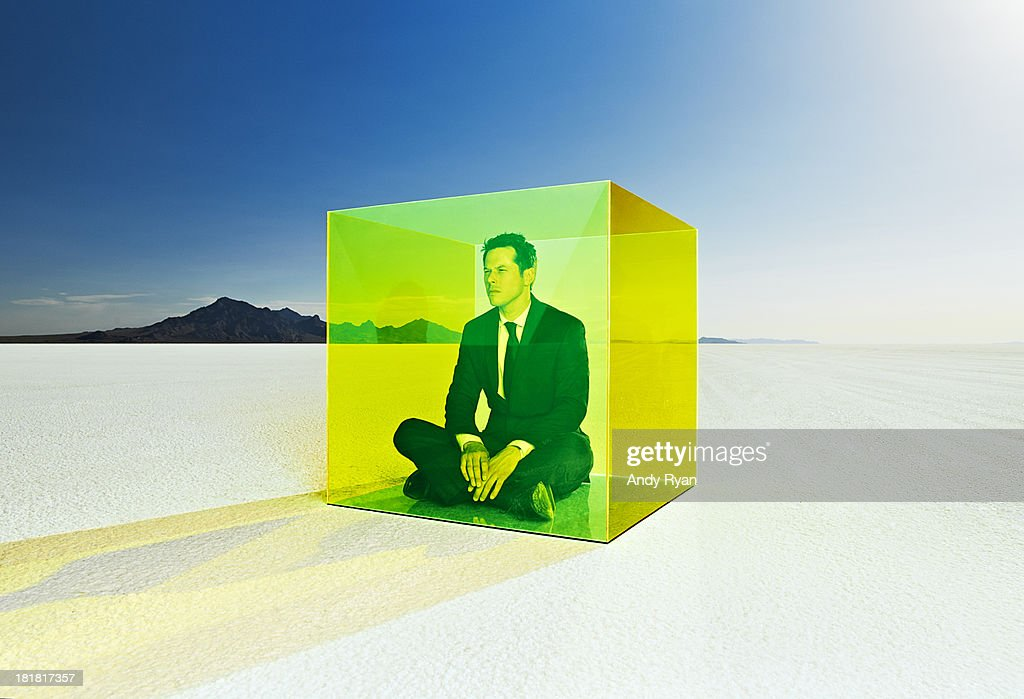 Man sitting in colored box on salt flats. : Stock Photo