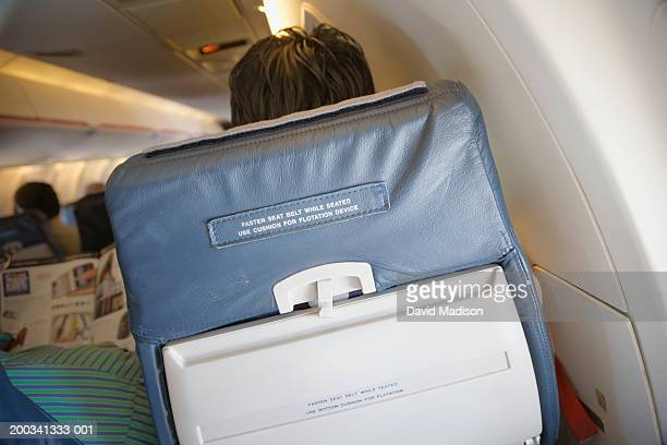 Man sitting in commercial airliner chair, rear view
