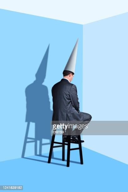 man sitting in corner wearing dunce cap - dunce cap stock pictures, royalty-free photos & images