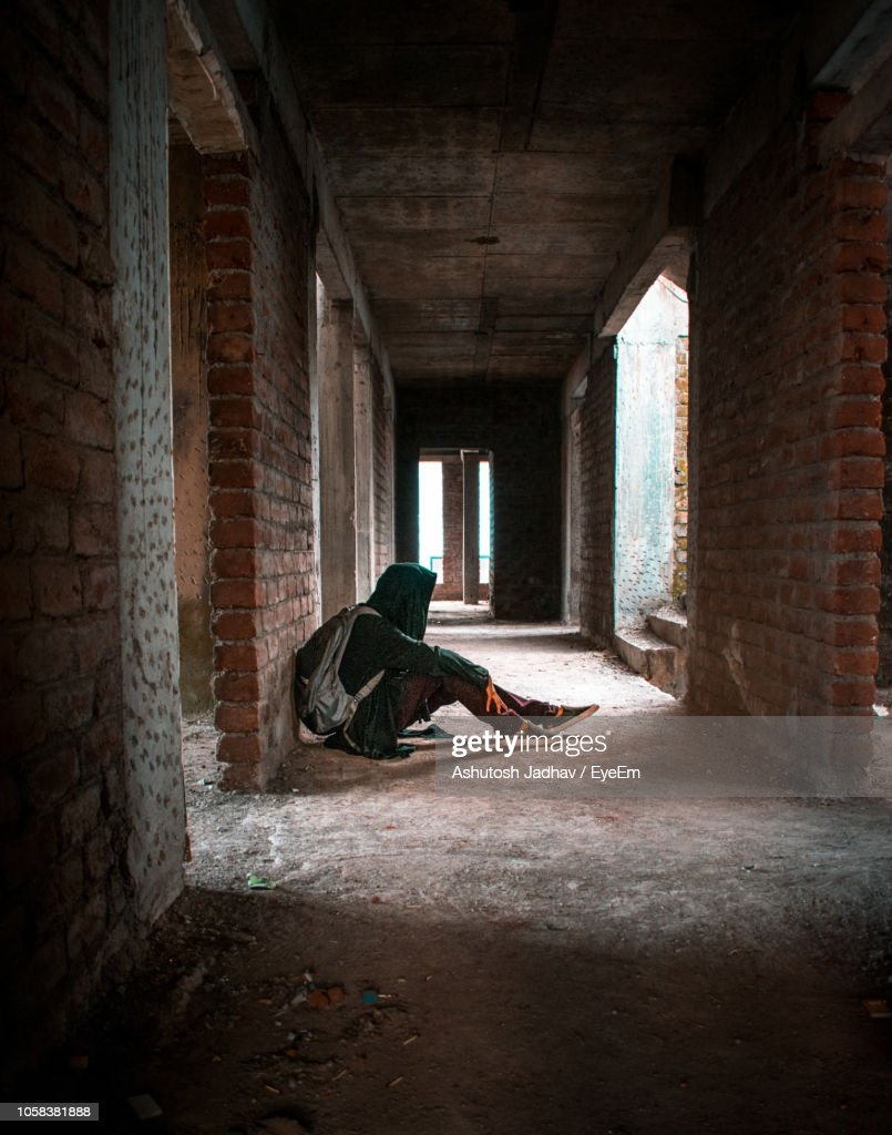 Man Sitting In Corridor Of Abandoned Building High Res Stock Photo Getty Images