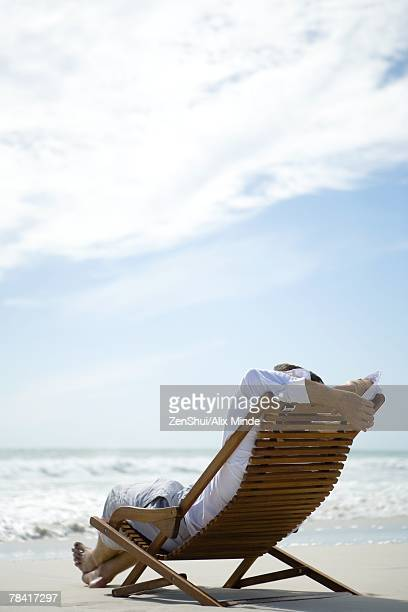 Man sitting in deck chair, facing sea
