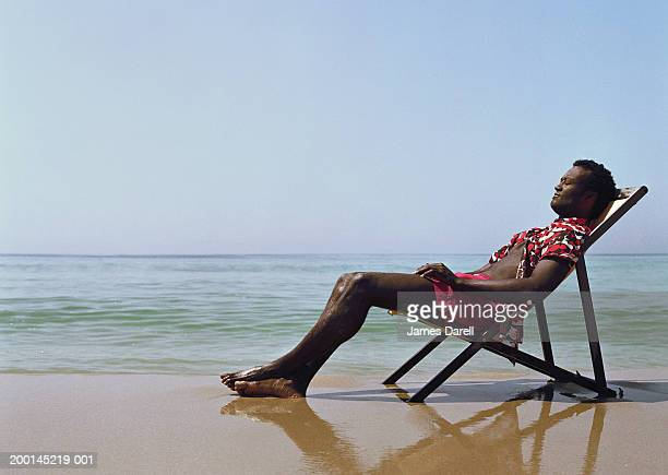 Man sitting in deck chair on beach, eyes closed, side view