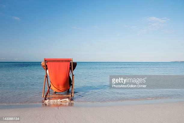 Man sitting in deckchair looking at ocean, rear view