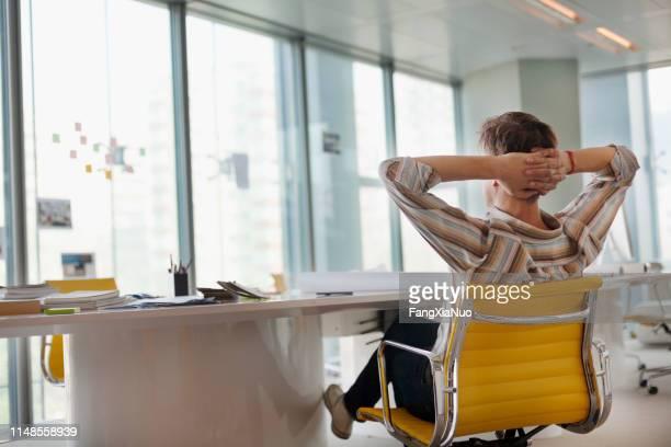 homem que senta-se no escritório do projeto que olha fora do indicador - cadeira - fotografias e filmes do acervo