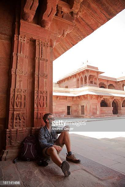 Man sitting in doorway of ancient building.