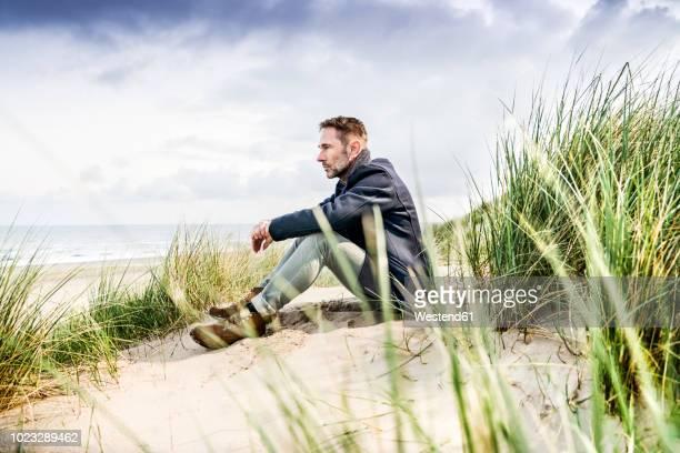 man sitting in dunes - barba por fazer imagens e fotografias de stock