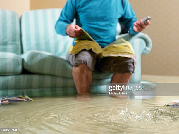 man sitting in flooded living room using phone, low section - flooding stock photos and pictures