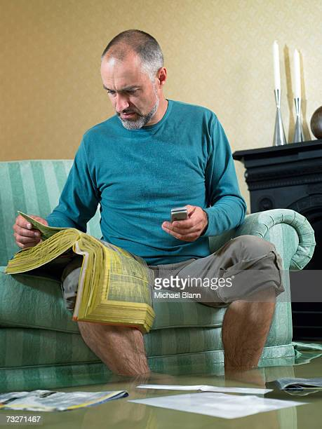 Man sitting in flooded living room using phone