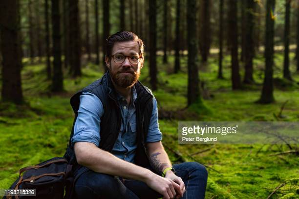 man sitting in forest - only mid adult men stock pictures, royalty-free photos & images