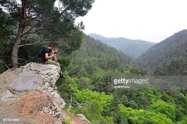 Mann sitzt im Wald mit Telefon