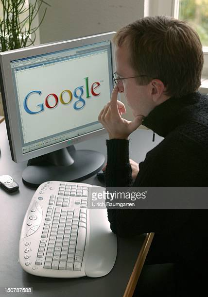 Man sitting in front of a display with the logo of the internet search engine Google