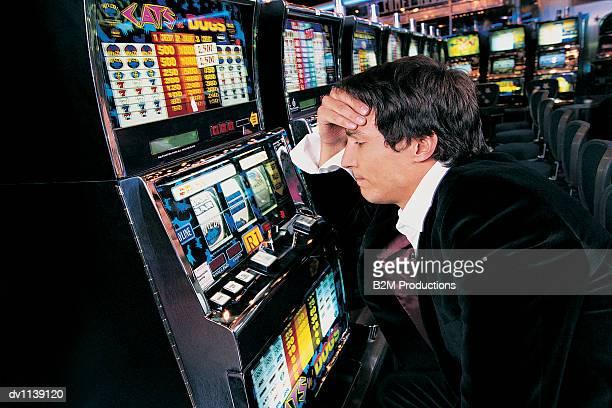 man sitting in front of a fruit machine with his hand on his head - niederlage stock-fotos und bilder