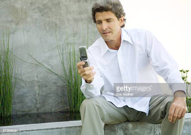 Man sitting in front of home, reading message on cell phone
