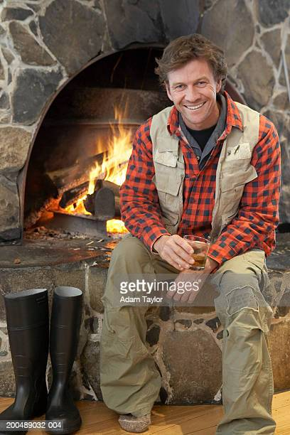 man sitting in front of log fire, smiling, portrait - cargo pants stock photos and pictures