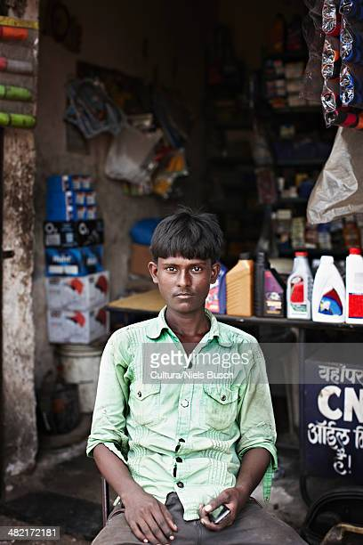 Man sitting in front of shop