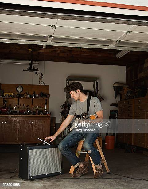 Man sitting in garage playing guitar and using tablet pc