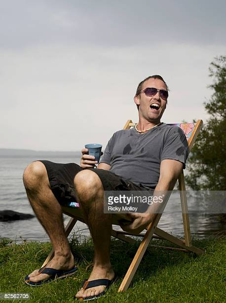 man sitting in garden chair in the rain - lap body area stock photos and pictures