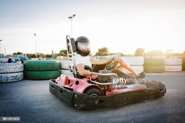 Man sitting in Go-cart against sky on sunny day