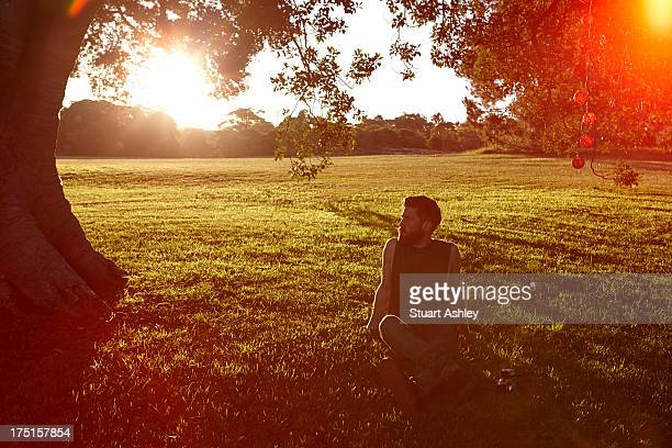 Man sitting in grassy park on sunset