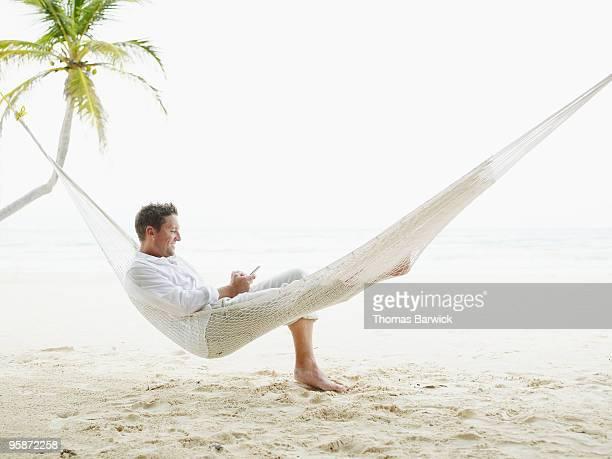 Man sitting in hammock on beach looking at palmtop