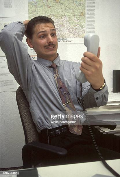 Man sitting in his office gesticulating with receiver