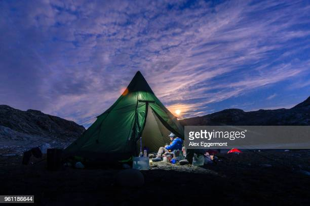Man sitting in illuminated tent at sunset, Narsaq, Vestgronland, South Greenland