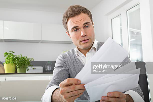 Man sitting in kitchen watching letters