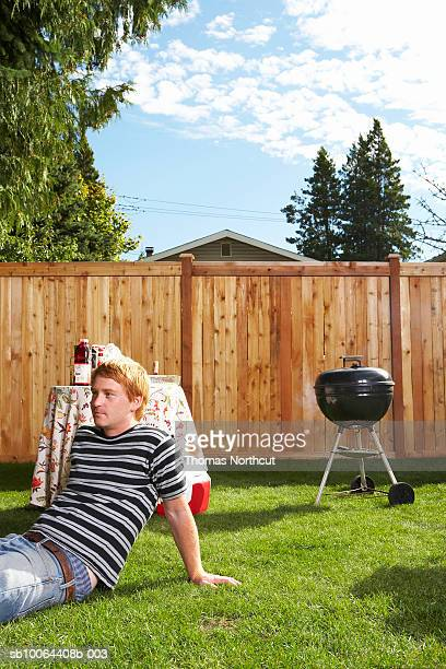 Man sitting in lawn, barbecue grill in background