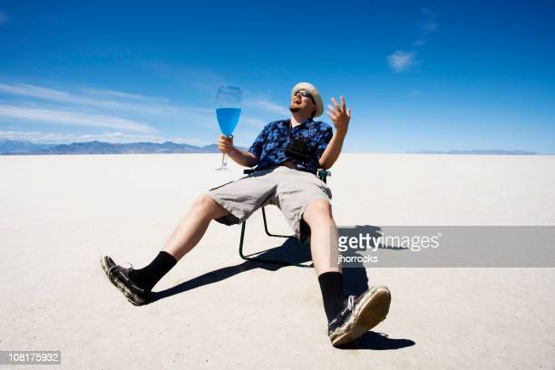 Man Sitting in Lawn Chair and Drinking at Salt Flats