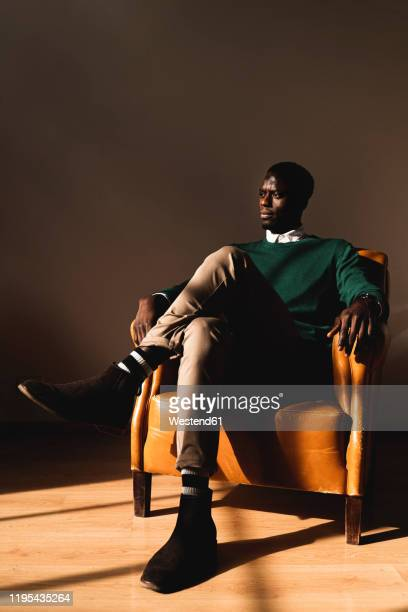 man sitting in leather armchair looking sideways - one man only stock pictures, royalty-free photos & images