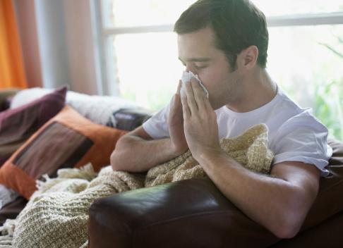 Man sitting in living room blowing nose - gettyimageskorea