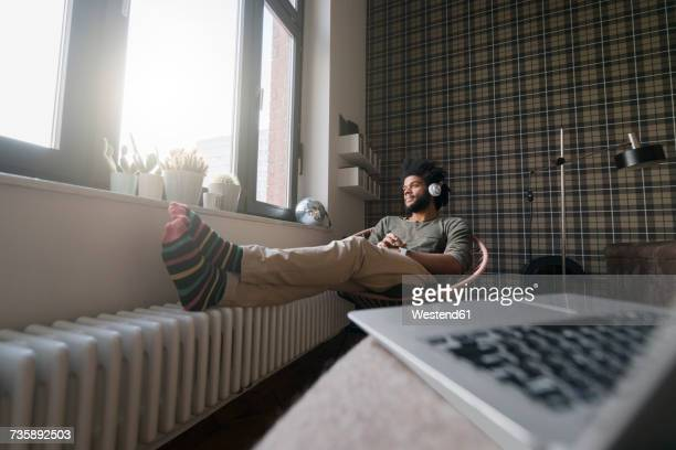 Man sitting in living room in armchair listening to music