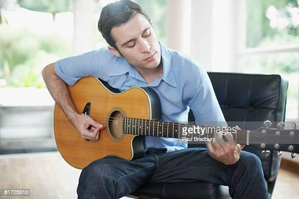 Mann sitzt im Wohnzimmer spielen Akustikgitarre