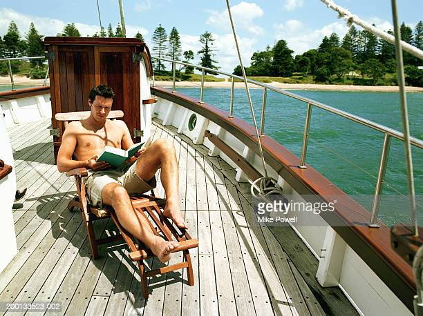 man sitting in lounge chair on sailboat, reading - sun lounger stock pictures, royalty-free photos & images