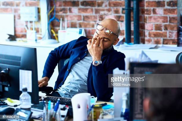 man sitting in modern office - ongerust stockfoto's en -beelden