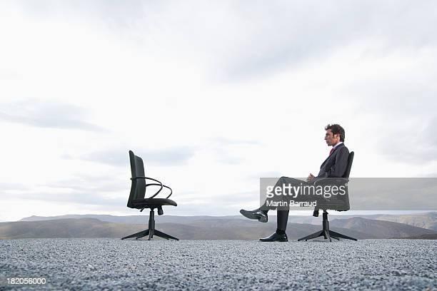 homme assis dans un fauteuil de bureau en plein air - chaise de bureau photos et images de collection