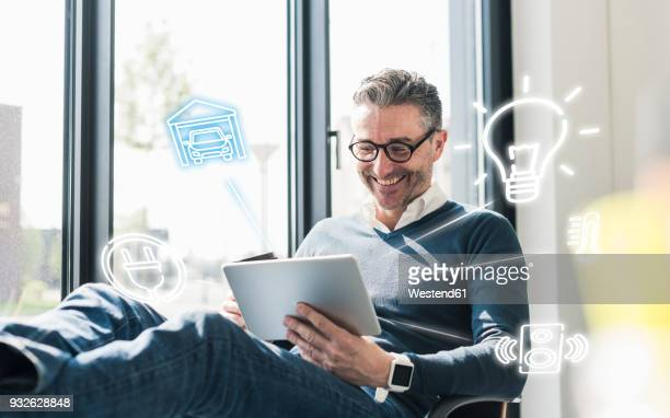 man sitting in office, using digital tablet to remote-control his smart home - home icon stock photos and pictures